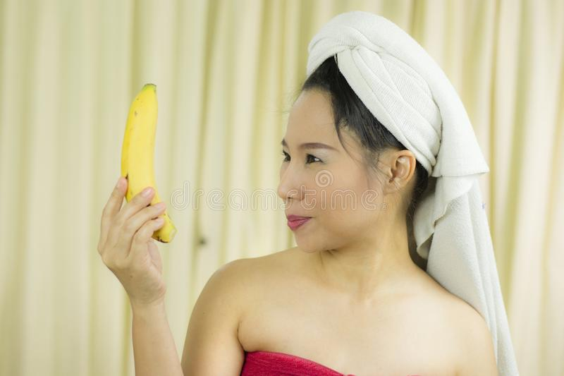 Kobiety mienia działania bananowy uśmiech śmieszny, smutny, jest ubranym spódnicę zakrywać jej pierś po obmycie włosy, Za zdjęcia royalty free