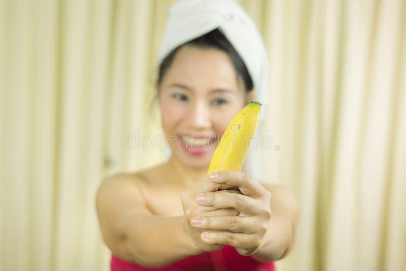 Kobiety mienia działania bananowy uśmiech śmieszny, smutny, jest ubranym spódnicę zakrywać jej pierś po obmycie włosy, Za obraz royalty free