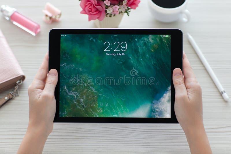 Kobiety mienia iPad Pro Astronautyczne szarość z tapety IOS 10 obraz royalty free