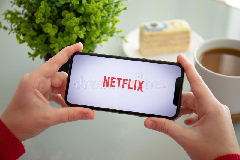 Kobiety mienia iPhone X z app Netflix leje się wideo zdjęcia royalty free