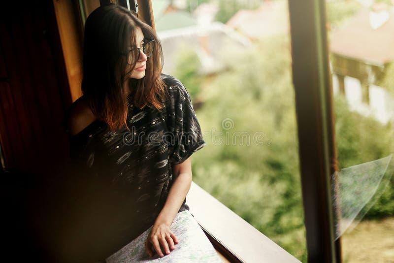 Kobiety mienia mapy obsiadanie przy okno z widokiem przy zadziwiającym mountai zdjęcie royalty free