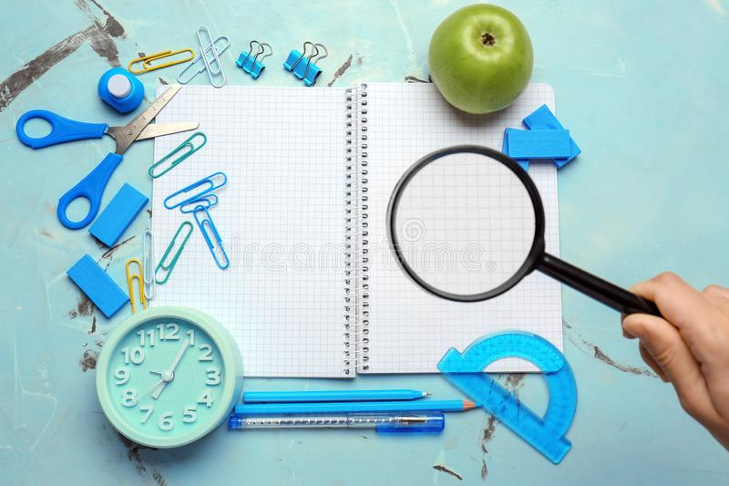 Kobiety mienia powiększać - szkło nad szkolnym materiały i budzikiem na lekkim tle obrazy stock