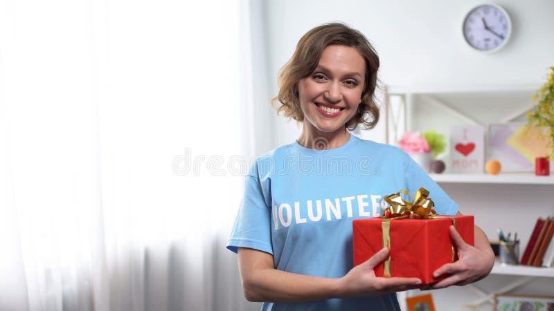 Kobiety mienia prezenta ochotniczy pudełko w rękach, ono uśmiecha się przy kamerą, dobroczynności darowizna obrazy royalty free
