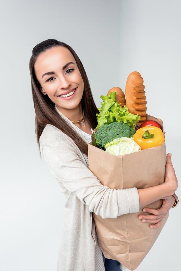Kobiety mienia sklepu spożywczego torba i ono uśmiecha się przy kamerą obrazy royalty free