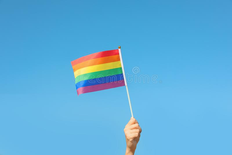 Kobiety mienia tęczy LGBT flaga przeciw niebieskiemu niebu zdjęcie royalty free