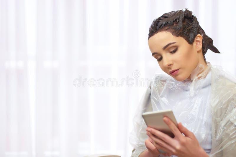 Kobiety mienia telefon, piękno salon obraz royalty free