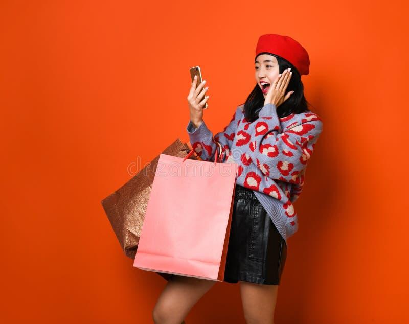 Kobiety mienia torba na zakupy i u?ywa? smartphone dla robi? zakupy online, robi zakupy poj?cie zdjęcie royalty free