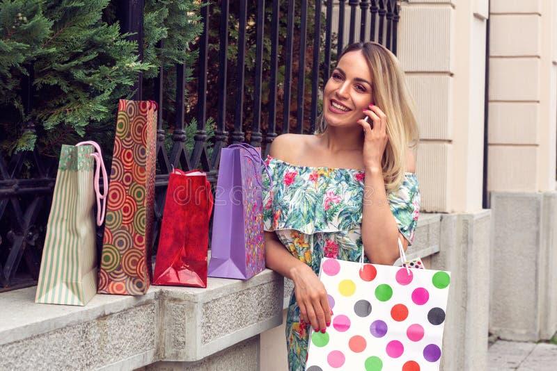 Kobiety mienia torby na zakupy, używać mądrze telefon i ono uśmiecha się podczas gdy stojący outdoors obraz stock