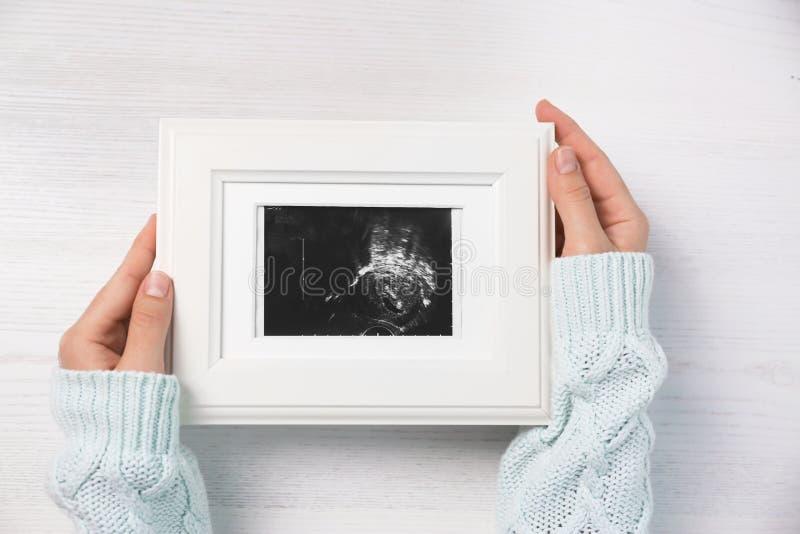 Kobiety mienia ultradźwięku fotografia dziecko nad drewnianym stołem, v obraz royalty free