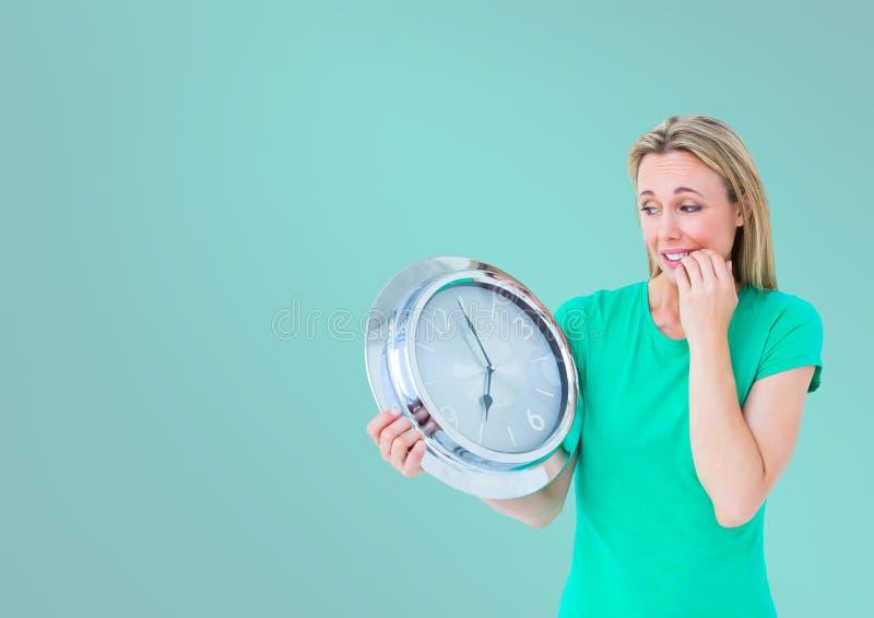 Kobiety mienia zegar przed turkusowym tłem obrazy stock