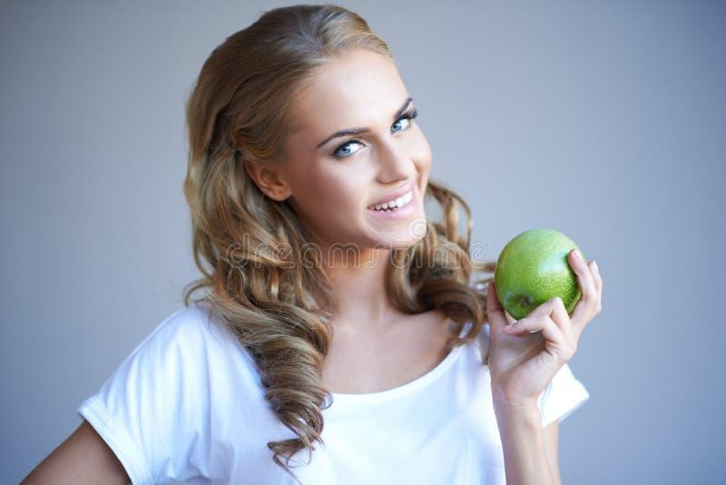 Kobiety mienia zieleni jabłko przeciw grey obrazy stock