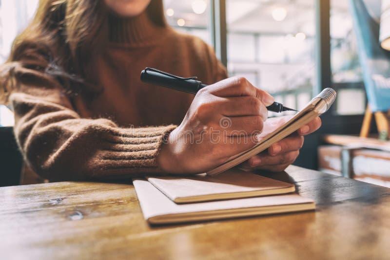 Kobiety mienie i pisać na pustym notatniku z fontanny piórem na drewnianym stole obrazy stock