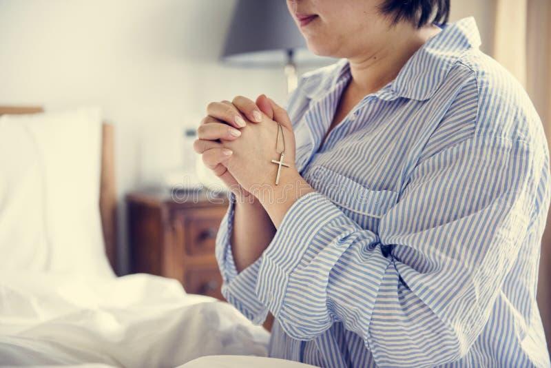 Kobiety modlenie siedzi na łóżku zdjęcia royalty free