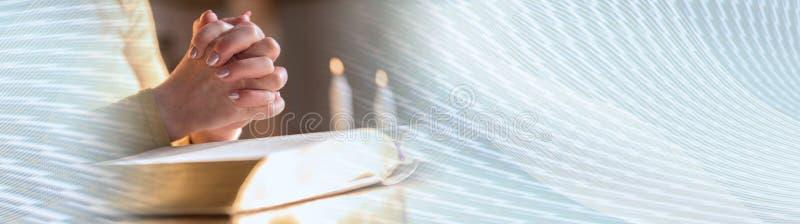 Kobiety modlenie z jej rękami nad biblią, ciężki światło sztandar panoramiczny obrazy stock