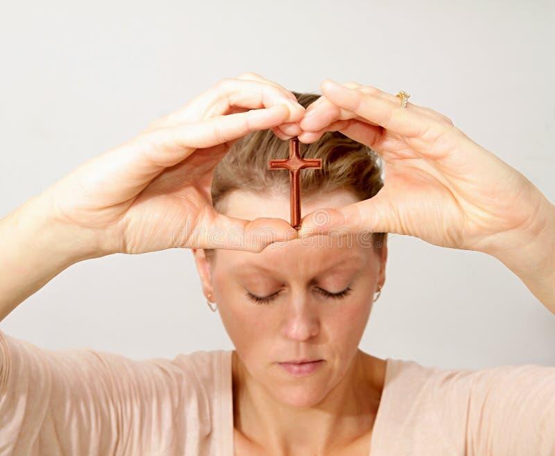 Kobiety modlenie z krzyżem w ona ręki obrazy stock