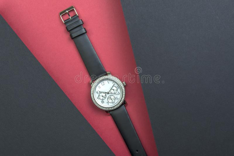 Kobiety mody wristwatch na czerwonym tle Dwa czarnego prześcieradła wznoszą się nad główny tło zdjęcia royalty free