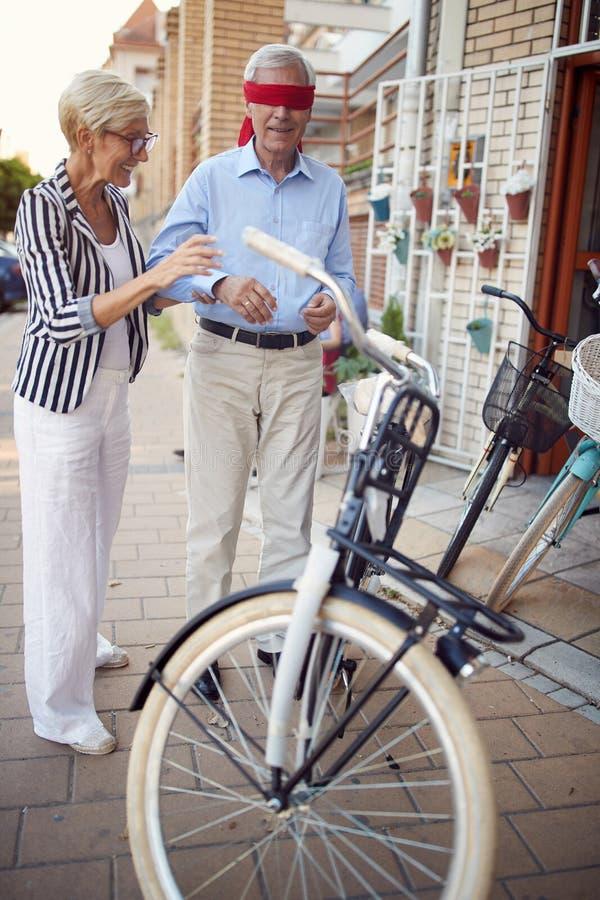 Kobiety nakrycia oczy mężczyzna dla niespodzianki z kupienie prezenta bicyklem obraz stock