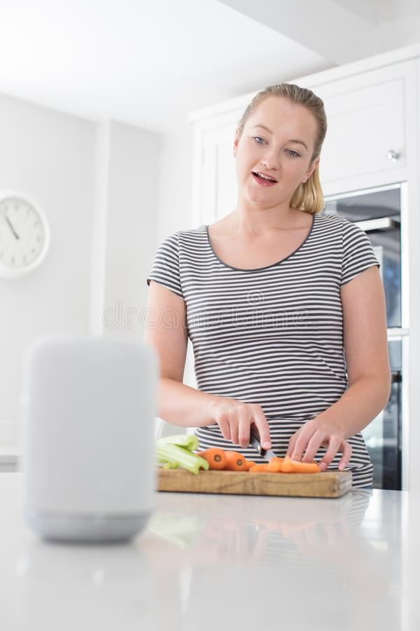 Kobiety narządzania jedzenie Pyta Cyfrowemu Pomocniczego pytanie W Domu zdjęcie stock