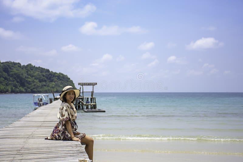 Kobiety Nosz? kapelusz na drewnianego mostu mola ?odzi w dennym i jaskrawym niebie przy Koh Kood, Trata w Tajlandia obraz royalty free