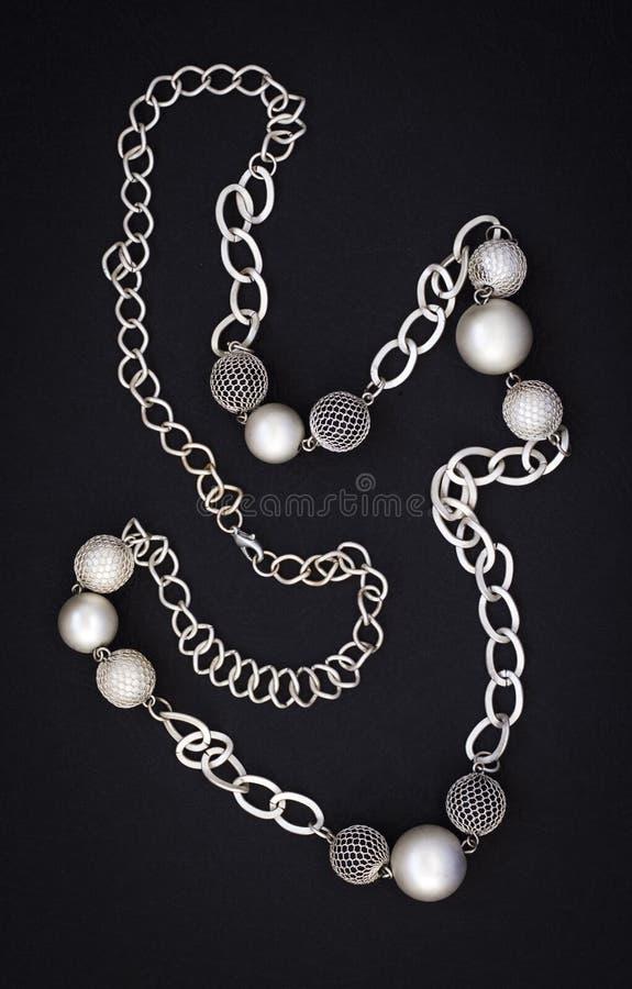 Kobiety nowożytna abstrakcjonistyczna kolia w postaci łańcuchu i piłki na czarnym tle fotografia royalty free