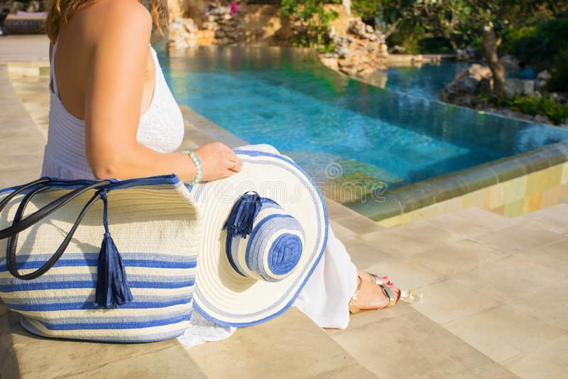 Kobiety obsiadanie basenem z eleganckim lato kapeluszem, torbą obok ona i obrazy royalty free