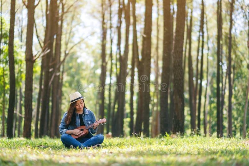 Kobiety obsiadanie i bawić się ukulele w outdoors fotografia stock