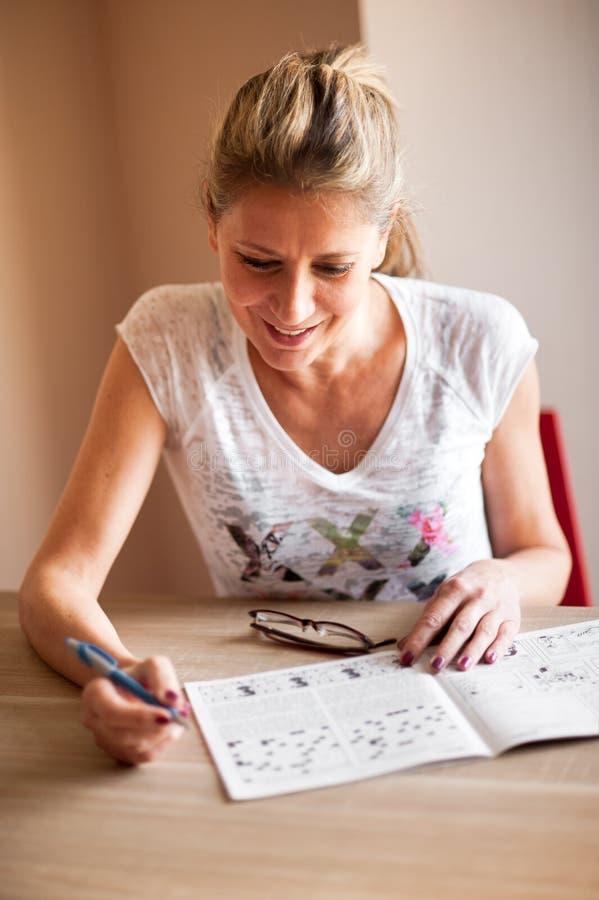 Kobiety obsiadanie i rozwiązywać crossword łamigłówki obrazy stock
