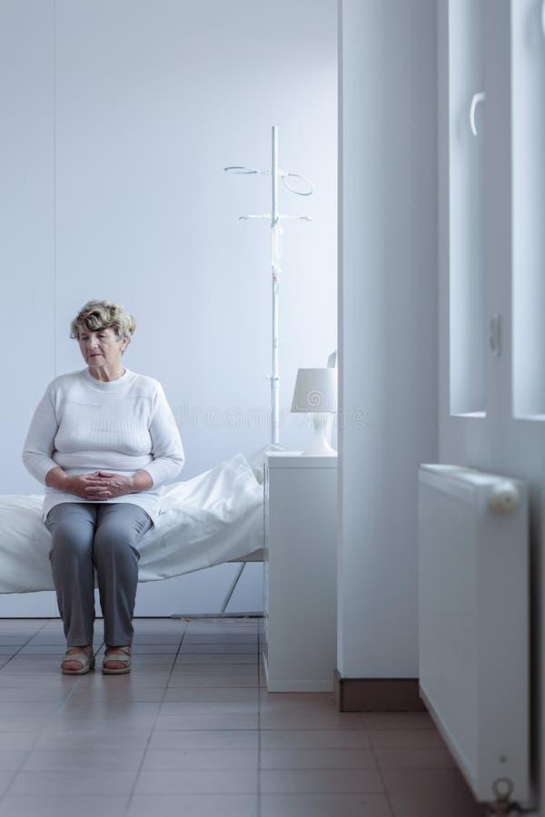 Kobiety obsiadanie na łóżku szpitalnym obrazy stock