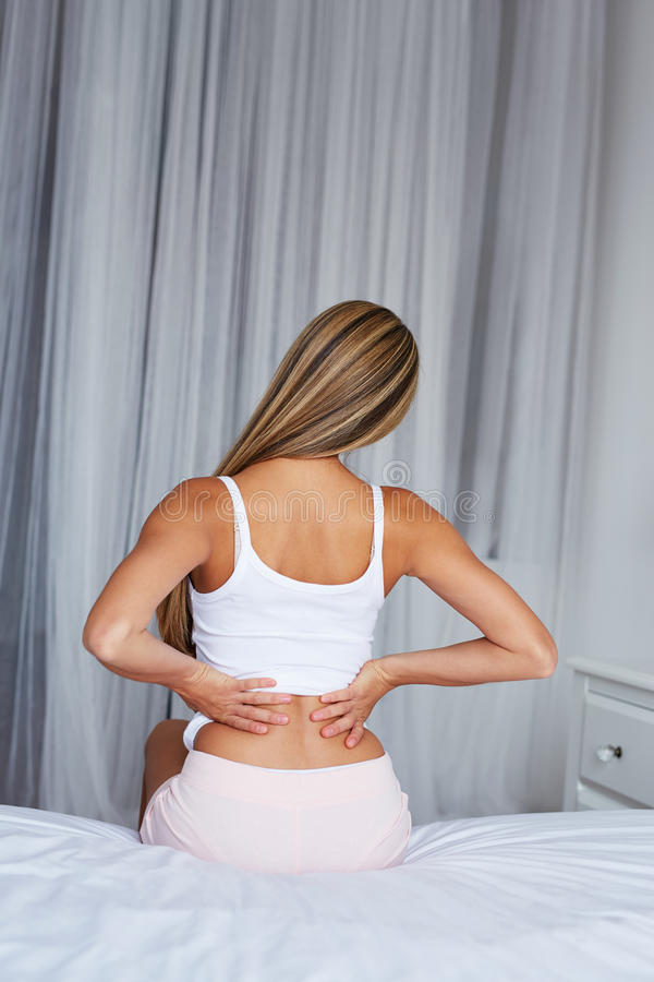Kobiety obsiadanie na łóżku z bólem pleców obraz royalty free
