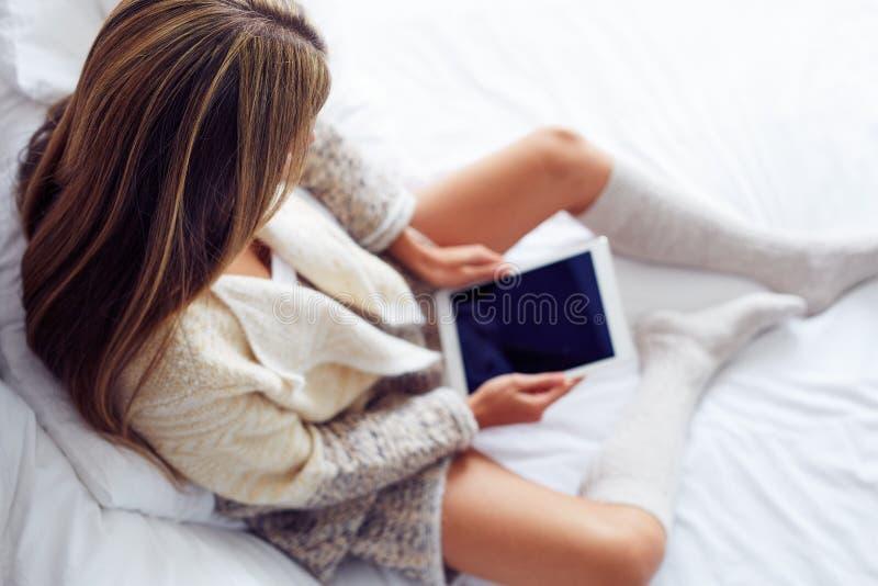 Kobiety obsiadanie na łóżku z jej pastylką obrazy stock
