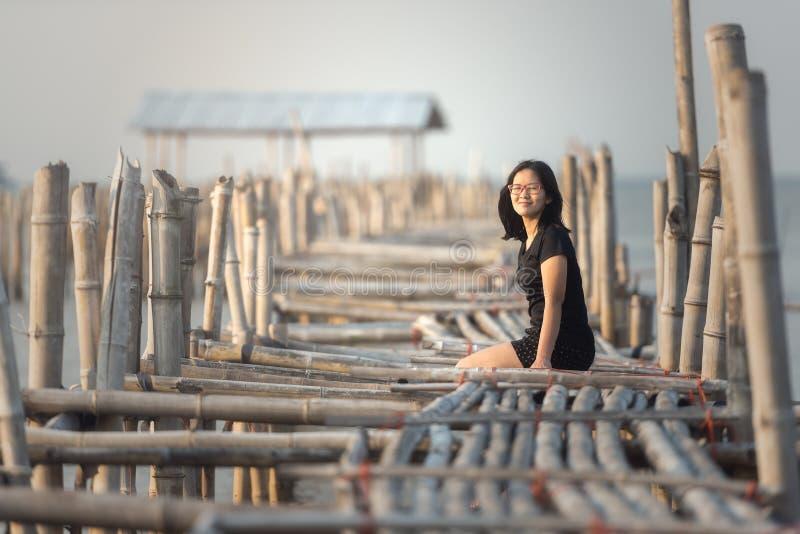 Kobiety obsiadanie na bambusa moscie fotografia stock