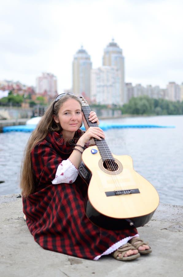 Kobiety obsiadanie na brzeg rzeki z gitarą w tradycyjny szkockim odziewa obraz royalty free