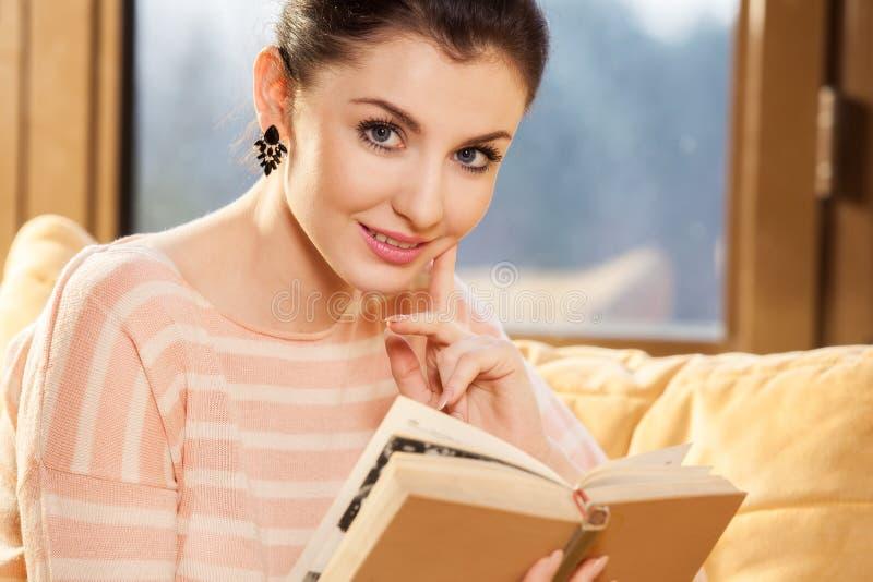 Kobiety obsiadanie na jej leżance w domu i czytający książkę zdjęcie stock