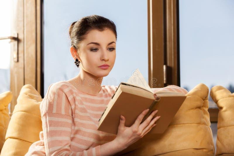 Kobiety obsiadanie na jej leżance w domu i czytający książkę obraz stock