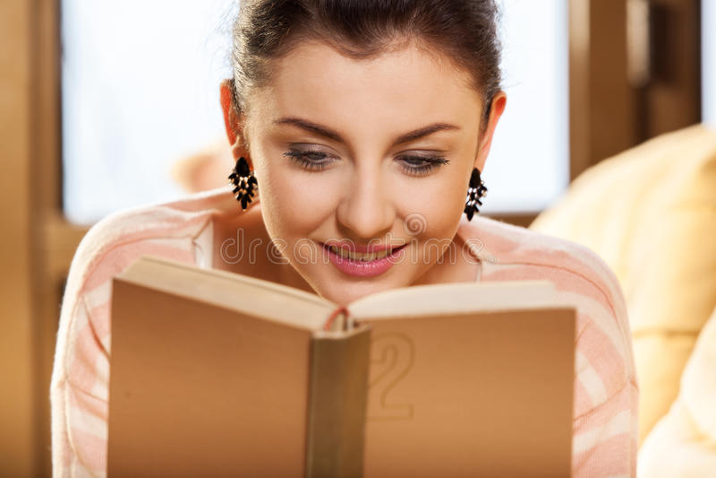 Kobiety obsiadanie na jej leżance w domu i czytający książkę zdjęcie royalty free