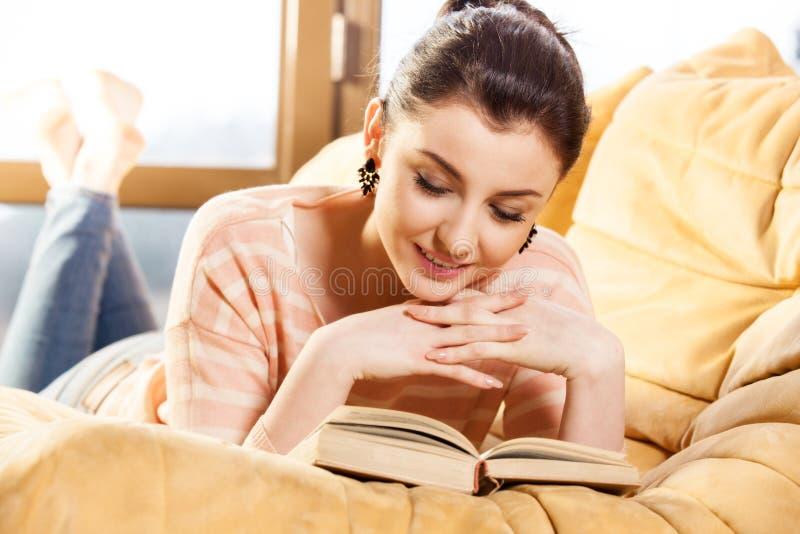 Kobiety obsiadanie na jej leżance w domu i czytający książkę obrazy royalty free