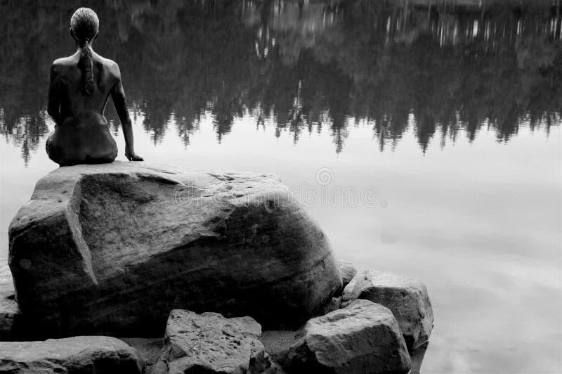 Kobiety obsiadanie na kamieniu blisko jeziornej czarny i biały fotografii fotografia stock