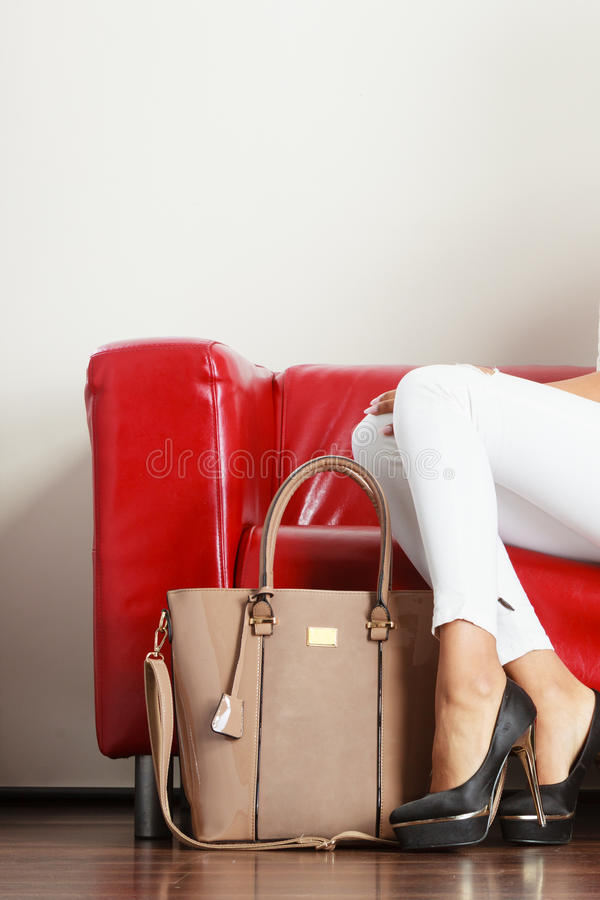 Kobiety obsiadanie na kanapie przedstawia rzemienną torbę obrazy royalty free