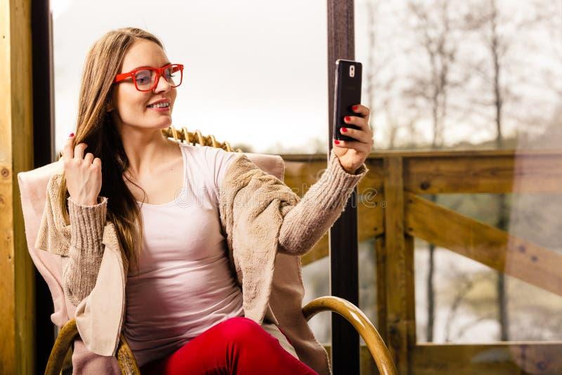 Kobiety obsiadanie na krześle robi selfie w domu obrazy stock