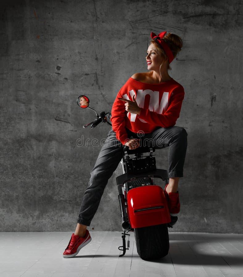 Kobiety obsiadanie na motocykl hulajnogi rowerowego retro pinup stylowym wskazuje palcu przy kątem w czerwonej bluzce i cajgach fotografia stock