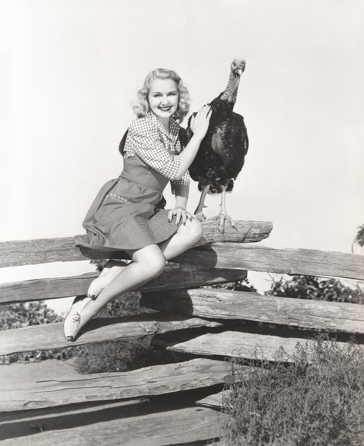 Kobiety obsiadanie na ogrodzeniu migdali jej indyka zdjęcie stock