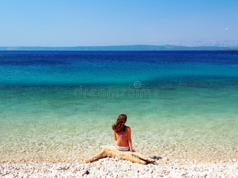 Kobiety obsiadanie na pięknej plaży zdjęcie royalty free