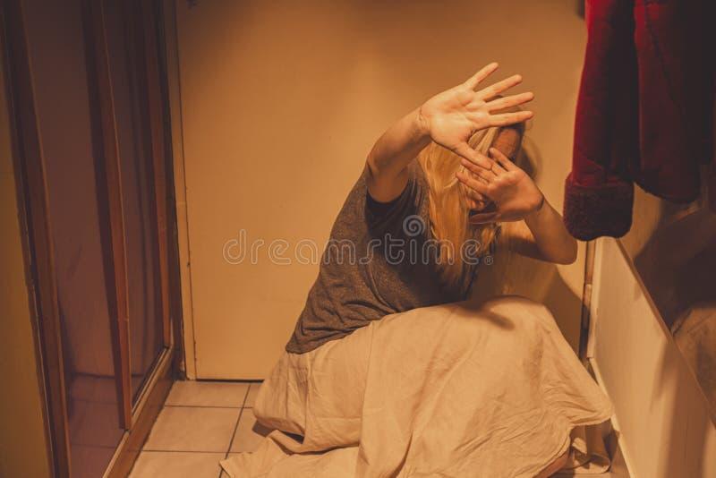 Kobiety obsiadanie na podłogowe płytki, mienie jej ręki przed jej ciałem zdjęcie royalty free