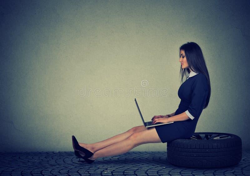 Kobiety obsiadanie na samochodowej oponie pracuje na laptopie fotografia royalty free