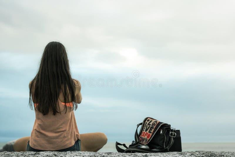 Kobiety obsiadanie na skale przy zmierzchem na Bakovern plaży, Kapsztad obraz stock