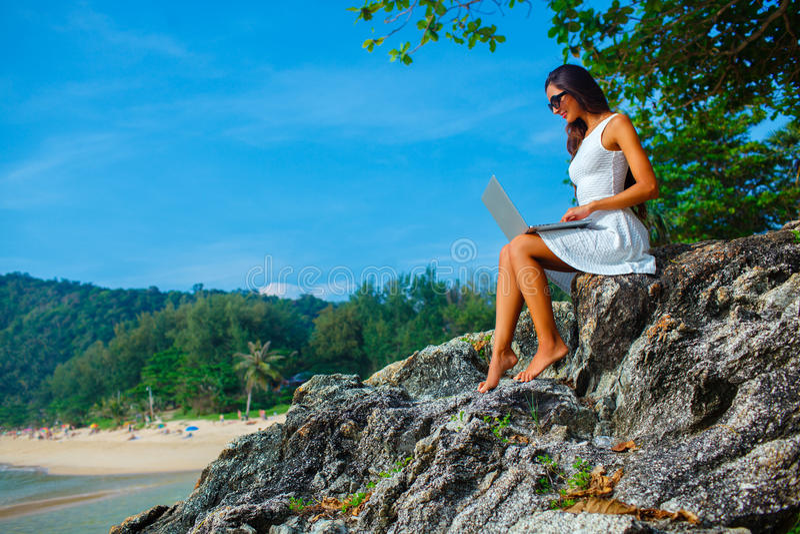 Kobiety obsiadanie na skale z laptopem obraz royalty free