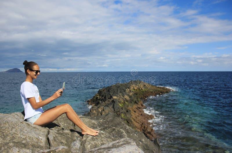Kobiety obsiadanie na skalistym brzeg z mapą fotografia royalty free