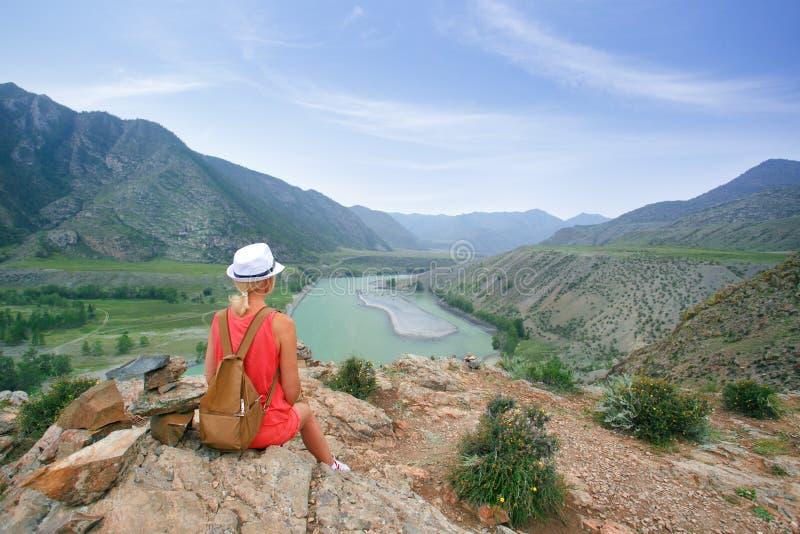 Kobiety obsiadanie na skalistym kamieniu i patrzeć góry w lecie obrazy royalty free
