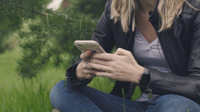 Kobiety obsiadanie na trawie z telefonem w ona ręki i mądrze zegarek zapas Pojęcie technologie w codziennym zdjęcia stock