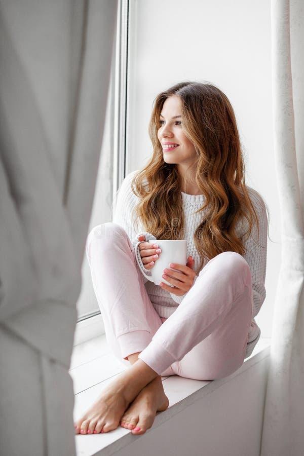 Kobiety obsiadanie na windowsill i mienia filiżance fotografia royalty free